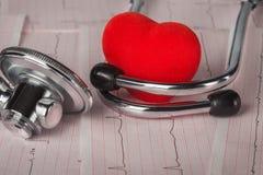 Medizinisches Stethoskop mit Kardiogramm- und Rotherzen Stockbild