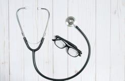 Medizinisches Stethoskop und Gläser auf weißem Schreibtisch Stockbild