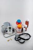 Medizinisches tonometer, phonendoscope, Pillen und Drogenflaschen auf Weiß Lizenzfreie Stockfotos