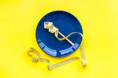 Medizinisches Verhungern für verliert Gewicht Leere Platte, Apfel und messendes Band auf Draufsicht des hellen gelben Hintergrund Stockfotografie