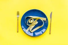 Medizinisches Verhungern für verliert Gewicht Leere Platte, Apfel und messendes Band auf Draufsicht des hellen gelben Hintergrund Stockbild