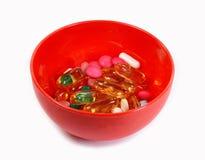 Medizinpillen herein in einer Schüssel lokalisiert auf Weiß Lizenzfreie Stockfotografie