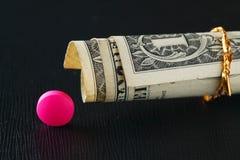 Medizinpillen und alte Banknote setzten an dunkle Szene Stockfotografie