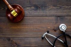 Medizinrecht, Gesundheitsgesetzeskonzept Hammer und Stethoskop auf dunkles hölzernes backgound Draufsicht kopieren Raum lizenzfreie stockbilder