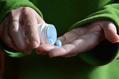 Medizinzeit Frau, die eine blaue Pille nimmt lizenzfreie stockfotos