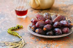 Medjoul - dried dates or kurma in a vintage plate and tea. Medjoul - dried dates or kurma in a vintage plate and tea on a rusty background Stock Images
