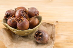 Medlars on an old wooden table Stock Photography