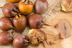 Medlars on an old wooden table Stock Image