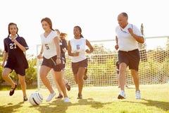 Medlemmar av kvinnlig högstadiumfotboll som spelar matchen royaltyfria bilder