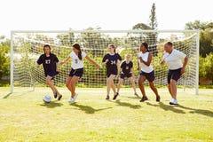 Medlemmar av kvinnlig högstadiumfotboll som spelar matchen arkivbild