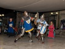 Medlemmar av riddarna av Jerusalem klubbar iklätt den traditionella harnesken av en riddare, slåss på svärd på natten i det gamma Royaltyfri Foto