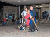 Medlemmar av riddarna av Jerusalem klubbar iklätt den traditionella harnesken av en riddare, slåss på svärd på natten i det gamma Arkivfoton