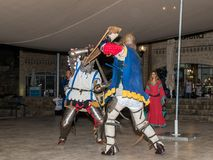 Medlemmar av riddarna av Jerusalem klubbar iklätt den traditionella harnesken av en riddare, slåss på svärd på natten i det gamma Fotografering för Bildbyråer