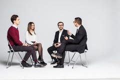 Medlemmar av stödgruppsammanträde i stolar som har möte på vit bakgrund royaltyfria bilder