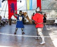 Medlemmedlemmen av den årliga festivalen av riddare av Jerusalem klädde, som riddare, slåss med svärd på cirkeln Royaltyfria Bilder