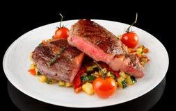 Medlet stekte biff med grönsaker på svart bakgrund Royaltyfri Fotografi