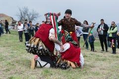 MEDOVO BULGARIEN - MARS 17, 2018: Folk i traditionella karnevalmaskeraddräkter på den Kukeri festivalen, Medovo by Royaltyfri Foto