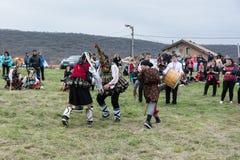 MEDOVO BULGARIEN - MARS 17, 2018: Folk i traditionella karnevalmaskeraddräkter på den Kukeri festivalen, Medovo by Fotografering för Bildbyråer