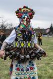 MEDOVO BULGARIEN - MARS 17, 2018: Folk i traditionella karnevalmaskeraddräkter på den Kukeri festivalen, Medovo by Arkivfoto