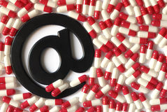 Meds by mail. The email symbol on a white and red capsules background Royalty Free Stock Photography