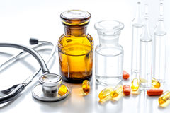 Meds and stethoscope on doctors workplace on white background Stock Image