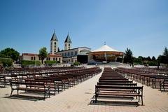 MEDUGORJE, BOSNIA-ERZEGOVINA - 4 LUGLIO 2016: Banchi ed altare dietro la chiesa di parrocchia di St James, il santuario della nos Immagine Stock