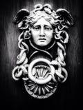 Medusa. Face on wooden door stock photo