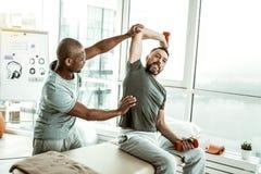 Medveten medicinsk arbetare som sträcker armen av hans patient arkivbilder