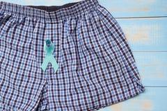 Medvetenhet för prostatacancer, ljus - strumpebandsorden med manlig kalsonger på blå träbakgrund royaltyfri foto