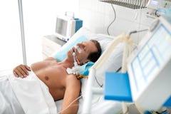 Medvetslös patient på den mekaniska ventilatorn som ligger i sjukhussäng fotografering för bildbyråer