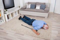 Medvetslös rörelsehindrad man som ligger på matta Royaltyfria Bilder