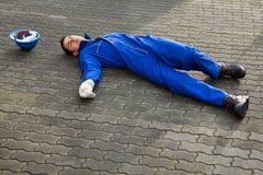 Medvetslös Repairman In Uniform Lying på gatan royaltyfri foto
