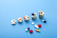 Medycyn pigułki, kapsuły i monety na błękitnym tle Fotografia Royalty Free