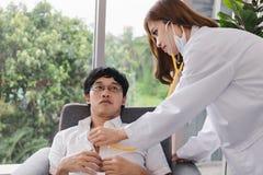 Medycyn potomstw lekarka egzamininuje Azjatyckiego męskiego pacjenta w medycznym biurze z stetoskopem obraz stock