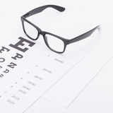 Medycyna i medyczni symbole - zamyka w górę studio strzału stół dla wzroku testa z szkłami nad nim zdjęcie stock