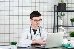 Medycyna, zawód, technologia i ludzie pojęć, - uśmiechnięta samiec lekarka z laptopem w medycznym biurze fotografia royalty free