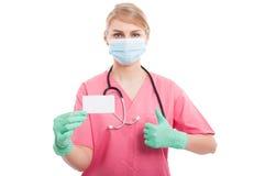 Medyczna pielęgniarki dama pokazuje pustą wizytówkę jak i obraz royalty free
