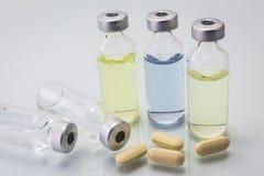 Medyczne buteleczki dla zastrzyka z żółtymi pigułkami, odizolowywają Obrazy Stock