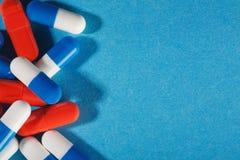 Medyczne pigułki błękitne i czerwone na jaskrawym tle Obrazy Stock
