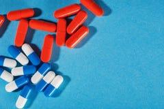 Medyczne pigułki błękitne i czerwone na jaskrawym tle Zdjęcia Stock