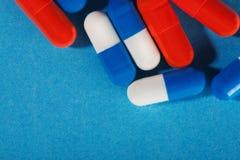 Medyczne pigułki błękitne i czerwone na jaskrawym tle Zdjęcie Stock