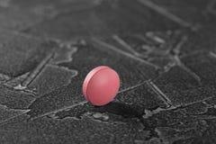 Medyczne pigułki czerwony kolor na szarości betonują tło Pojęcie medycyna vite zdjęcie stock