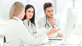 Medyczni profesjonali?ci siedzi przy biurowym biurkiem dyskutuj? co? obrazy stock