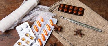 Medyczny bandaż, pigułki i termometr na drewnianym tle, z bliska Fotografia Royalty Free