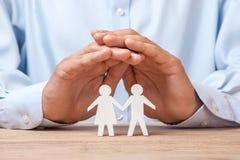 Medyczny lub podróż ubezpieczenie Mężczyzna zakrywa jego rodziny z mężczyzna i kobietą obraz stock