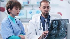 Medyczny naukowiec z piel?gniark? w nowo?ytnych biurowych patrzeje MRI i CT obrazach cyfrowych zbiory
