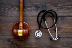 Medyczny prawo, zdrowia prawa pojęcie Młoteczek i stetoskop na ciemnego drewnianego backgound odgórnym widoku Obrazy Stock