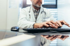 Medyczny profesjonalista używa komputerową klawiaturę w klinice Fotografia Stock