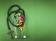 Medyczny stetoskop i chrześcijanina krucyfiks z pigułkami zdjęcie royalty free