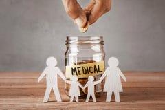 medyczny Szklany słój z monetami i inskrypcją jest medyczny i symbolu rodzina z dziećmi zdjęcia stock